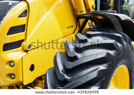 yellow bulldozer with a big wheel. focus on the wheel - stock photo
