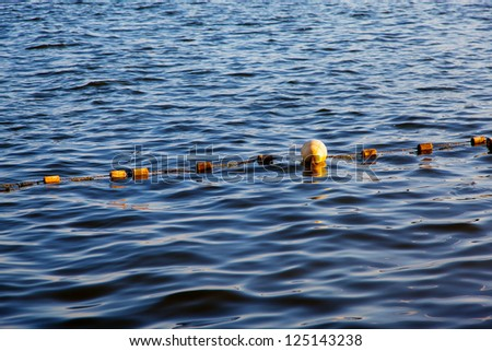 Yellow buoy on water - stock photo