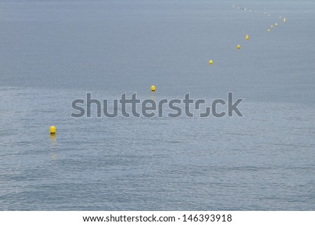 Yellow buoys line on sea - stock photo