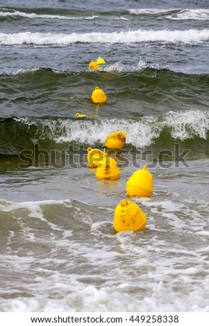 Yellow buoys on the surface of the sea of Baltic define the boundary of the safe swimming at the beach in Kolobrzeg in Poland - stock photo