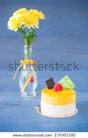 Yellow cake decorated with berries, close teacup and flowers in a glass vase on a wooden blue background - stock photo