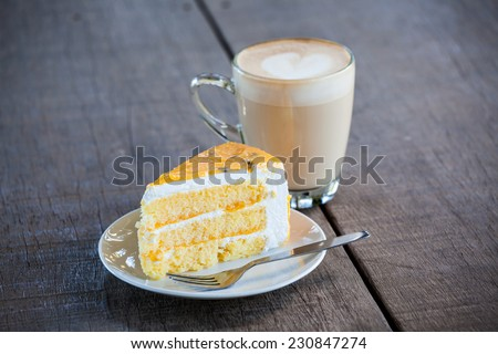 Yellow cake with cup of latte coffee on old wood table  - stock photo