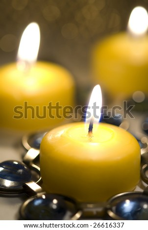Yellow candle burns with  candles behind it.