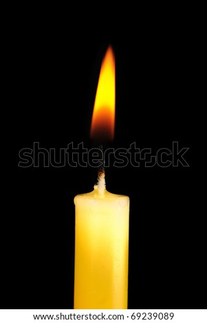 Yellow  candle in dark room - stock photo