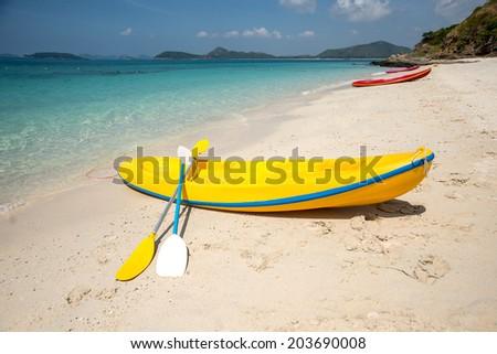 Yellow canoe on the seashore - stock photo