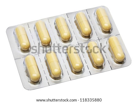 Yellow capsules in aluminum foil strips - stock photo
