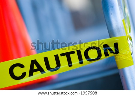 Yellow caution tape on stair rail with orange traffic cone behind, very shallow depth of field. - stock photo