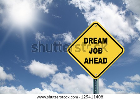 Yellow cautionary road sign Dream Job Ahead on beautiful sky background