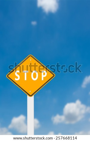 yellow cautionary road sign stop against a beautiful sky background - stock photo