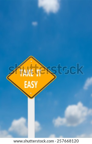 yellow cautionary road sign take it easy against a beautiful sky background - stock photo