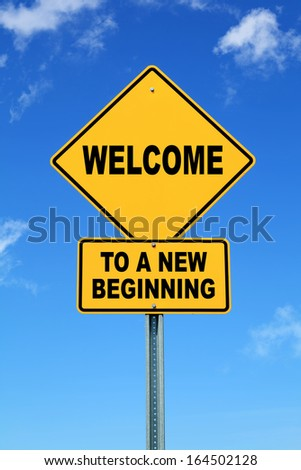 Yellow cautionary road sign Welcome to a new beginning - stock photo