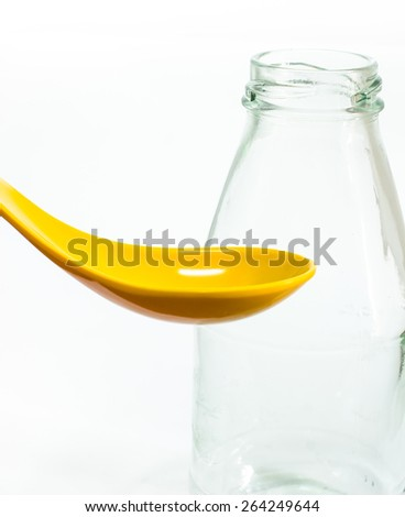 Yellow ceramic spoon and glass bottles - stock photo