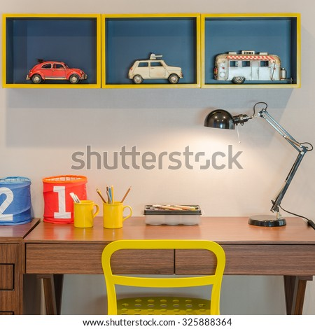 yellow chair and wooden desk with modern black lamp in kid's bedroom - stock photo