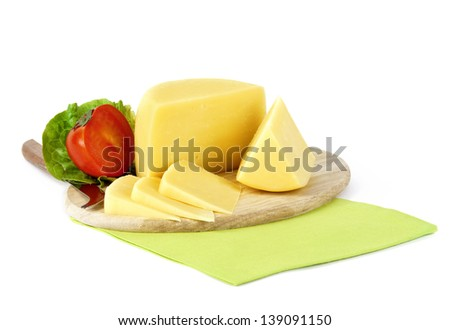 yellow cheese cut in pieces on a wooden plate - stock photo
