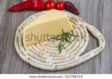 Yellow cheese triangle with rosemary herbs on the wood background