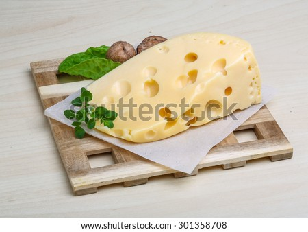Yellow cheese with oregano leaves on the wood background - stock photo