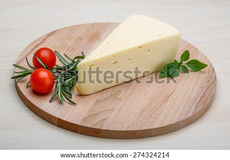 Yellow cheese with rosemary on the wood background