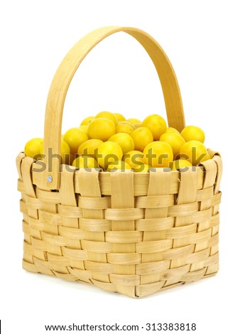 Yellow cherry plums in basket on a white background - stock photo