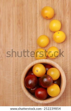 yellow cherry tomatoes over wooden background - stock photo