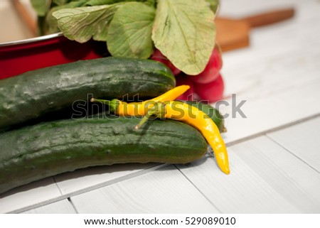 Yellow chili pepper and cucumber on kitchen table