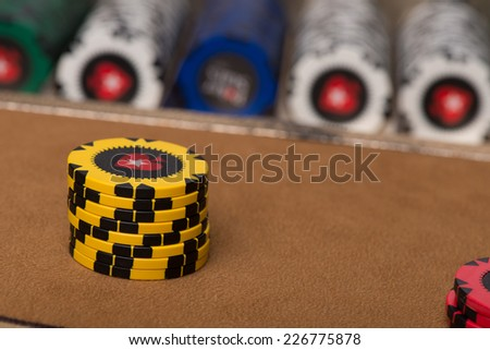 yellow chips in pile on table with red blue and shite chips  selective focus - stock photo