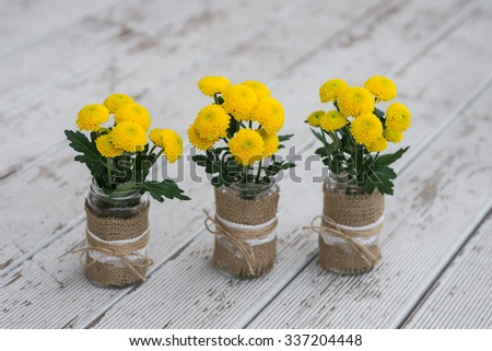 Yellow chrysanthemum flowers are in a vase with decor