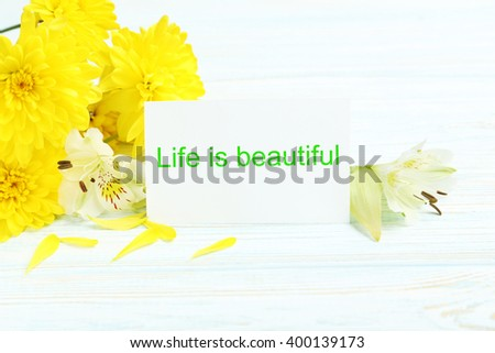 Yellow chrysanthemum flowers with card on a blue wooden table