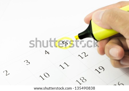 Yellow circle. Mark on the calendar at 5. - stock photo