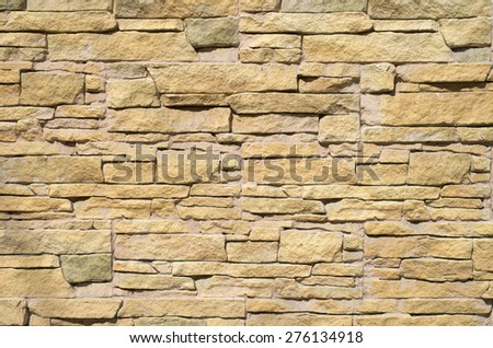 Yellow cladding tiles imitating stones in sunny day