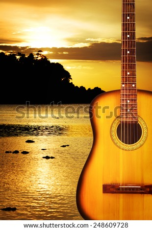 yellow classic acoustic guitar, on nature background - stock photo