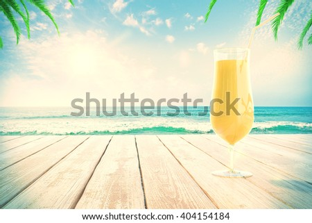 Yellow cocktail glass on wooden surface at the beach with palm trees. 3D Rendering - stock photo