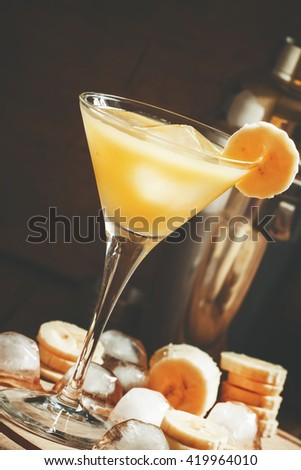 Yellow cocktail with whiskey, banana and ice, black background, selective focus