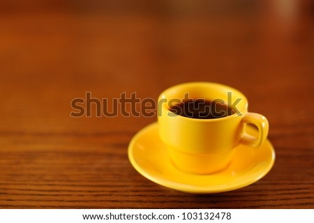 Yellow Coffee Cup on Wooden Table. Yellow demitasse coffee cup and saucer on a wooden table. Shallow DOF. Space for copy. - stock photo