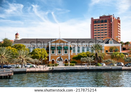 Yellow Colonial Building at Willemstad, Curacao, Caribbean with seafront esplanade on a sunny blue sky day - stock photo