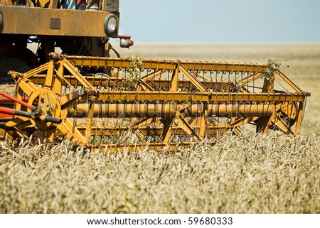 Yellow combine harvester working in a wheat field - stock photo