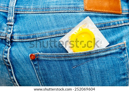 Yellow condom in a jeans pocket. - stock photo