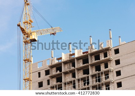 Yellow construction crane and unfinished brick house on a background of blue sky - stock photo