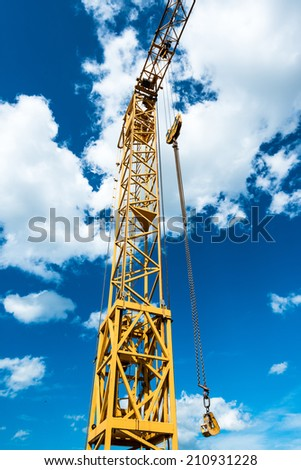 Yellow construction crane detail against great blue cloudy sky - stock photo