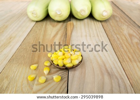 Yellow corn in a wooden spoon / kernels on wooden spoon isolated over corn background on wooden floor. - stock photo