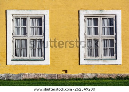 Yellow cracked wall with two white windows - stock photo