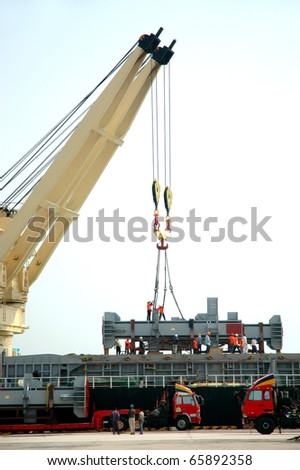 yellow crane and construction worker on ships freight - stock photo