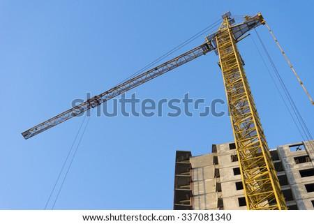yellow crane near the building under construction - stock photo