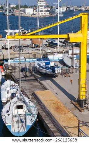 Yellow crane, sailing yachts and pleasure boats, Varna port, Bulgaria - stock photo