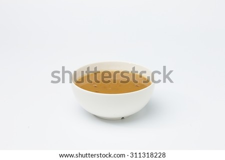 Yellow cream soup in white cup isolated on white background.