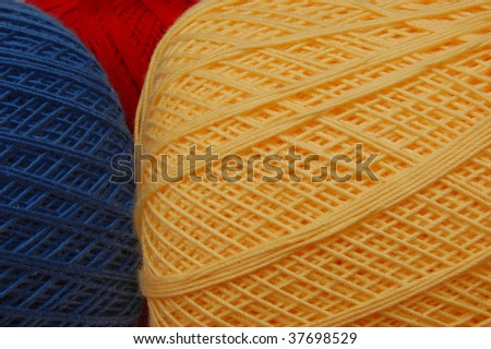Yellow crochet thread with blue and red in the background