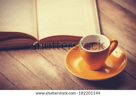 yellow cup of the coffee and vintage book. Photo with filter as a retro color image style. - stock photo