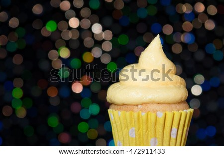 Yellow cupcake with swirl frosting with a bokeh background