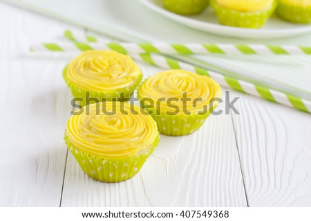 Yellow cupcakes in light green paper baking cups on white wooden table and striped drinking straws. Selective focus - stock photo