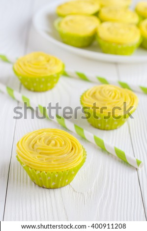 Yellow cupcakes in light green paper liners on wooden table. Selective focus