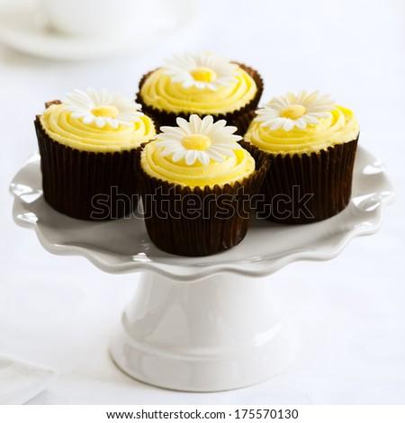 Yellow cupcakes on a white cakestand - stock photo
